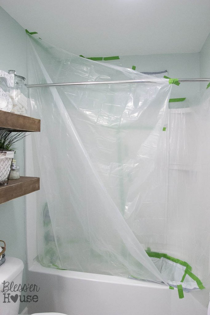 Here is how to cover your entire shower with a drop cloth to avoid any major mistakes or messes! How to Spray Paint Shower Fixtures (without the plumbing work) | Bless'er House