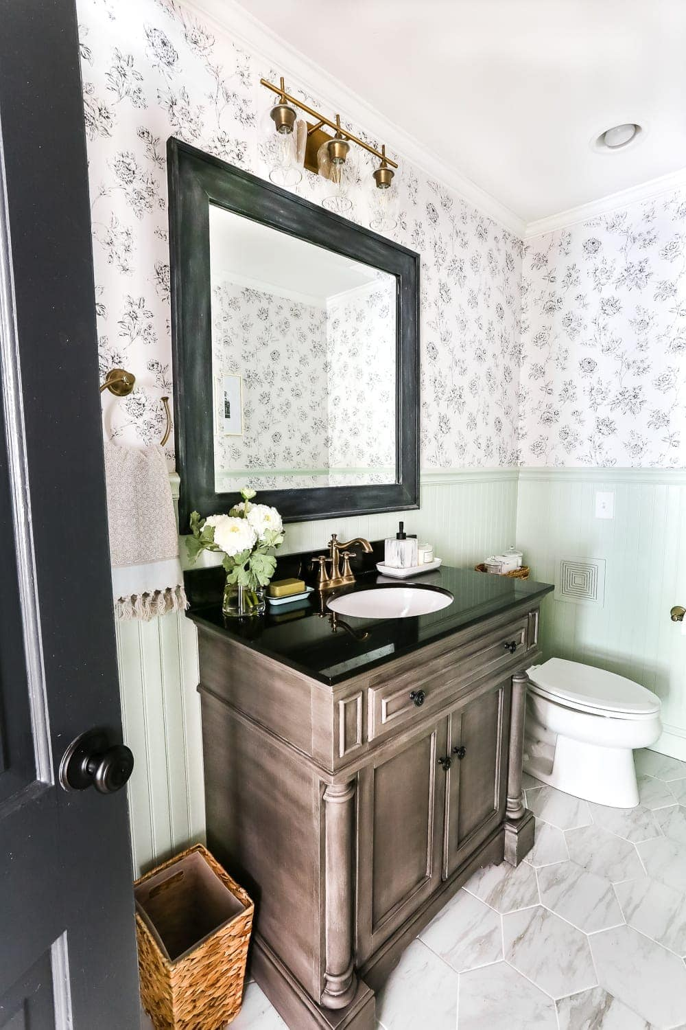 Mint, black, and white powder room with floral wallpaper and aged brass