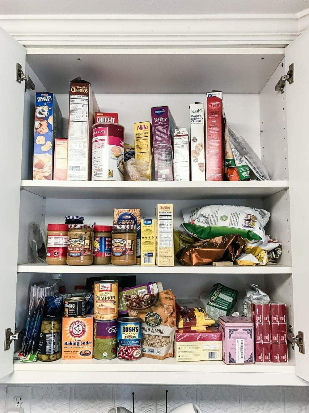 Pantry Cabinet Organization and Free Printable Label Set | blesserhouse.com - A cabinet gets a drastic organization makeover using inexpensive IKEA jars / baskets, hanging storage, and a free pantry label printable set. #organization