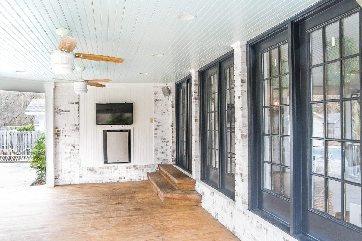 limewashed brick back porch with haint blue ceiling and black doors