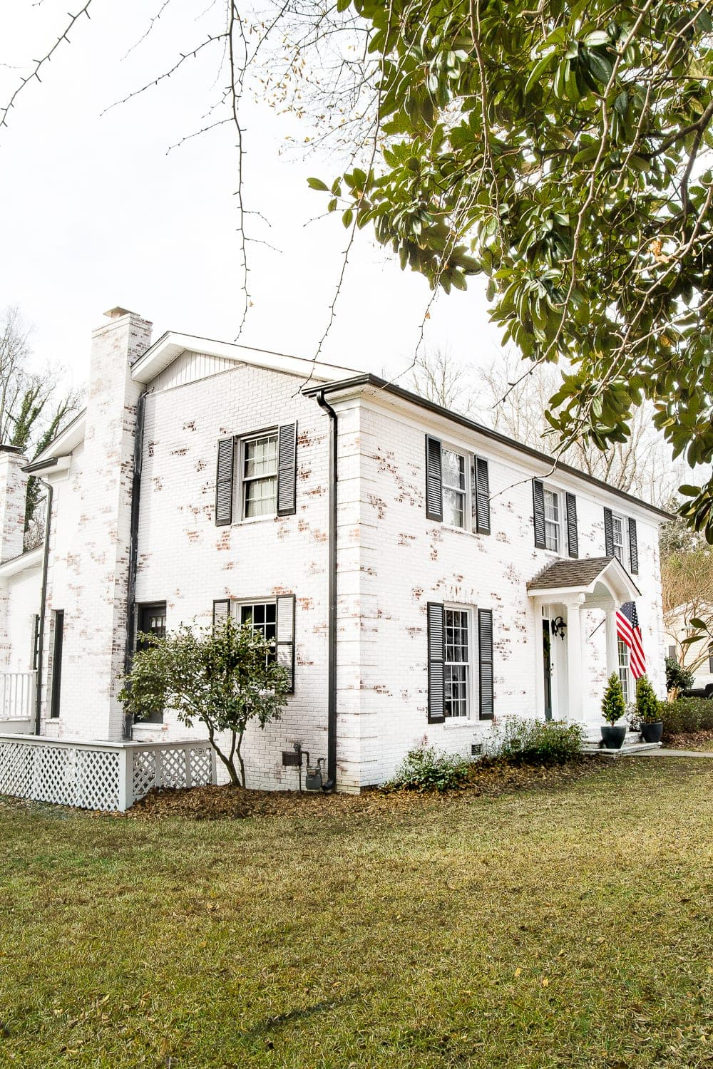 Limewashed Brick Exterior Makeover Reveal | blesserhouse.com - A brick fixer upper colonial house gets a limewashed brick exterior makeover using Romabio Classico Limewash in Bianco White. #limewashedbrick #exteriormakeover #curbappeal #exteriorpaint