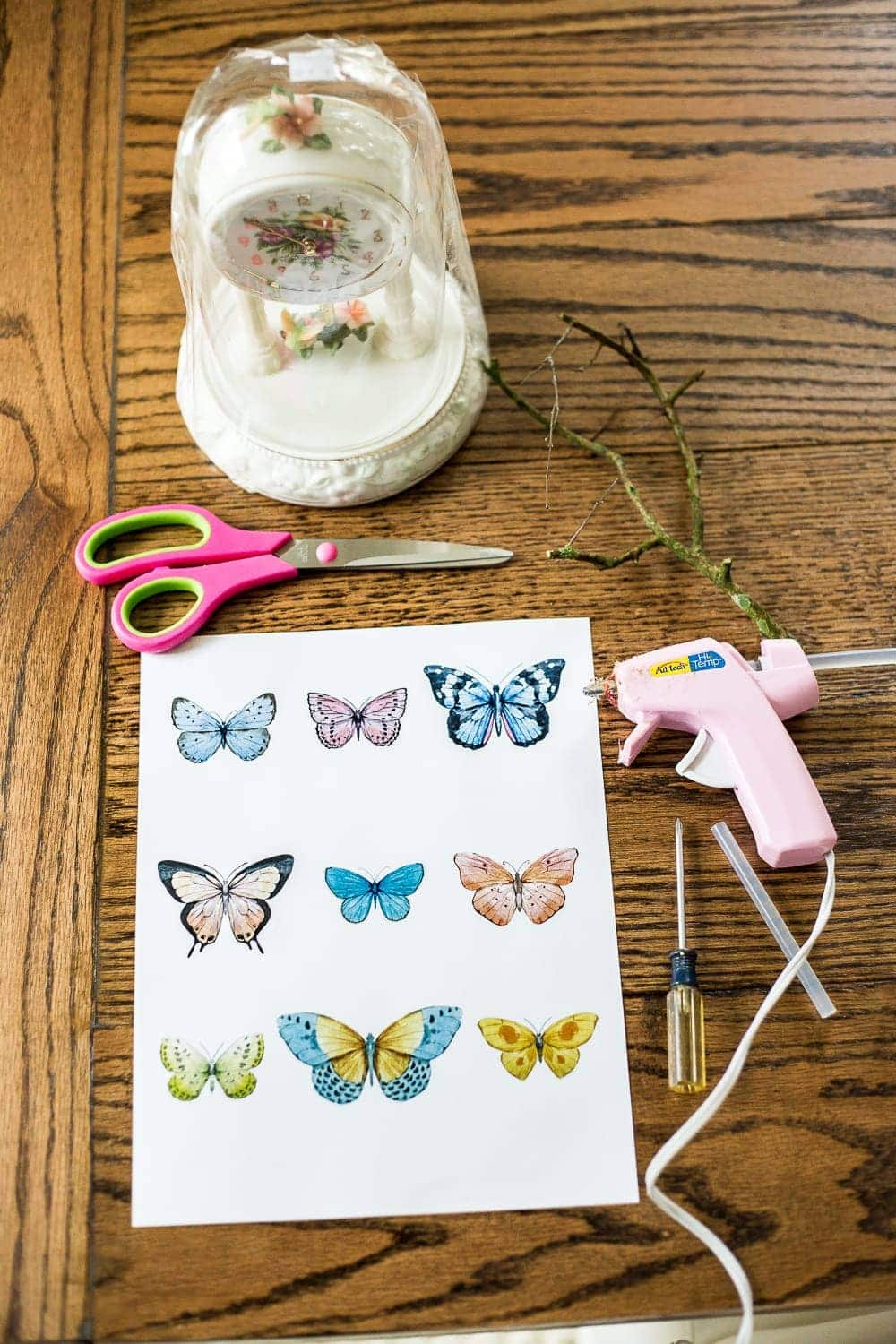 How to turn a cheap, thrifted dome clock into a Victorian style butterfly terrarium cloche with free printables to make your own paper butterflies for spring. #springdecor #thrifteddecor #cloche #springvignette #girlydecor #butterflies
