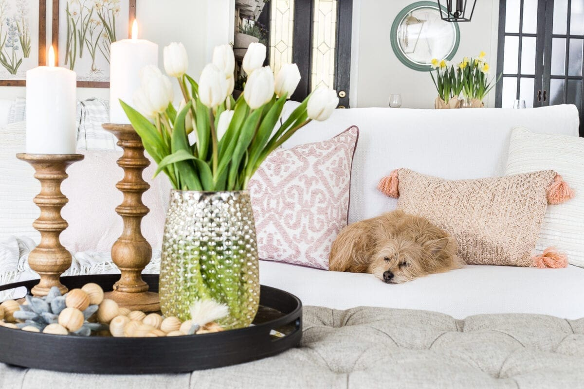 A living room gets a spring refresh with simple florals, candle light, and light fabrics.  #springdecor #livingroom #springlivingroom #springaccents #livingroomdesign #livingroomdecor #budgetdecor