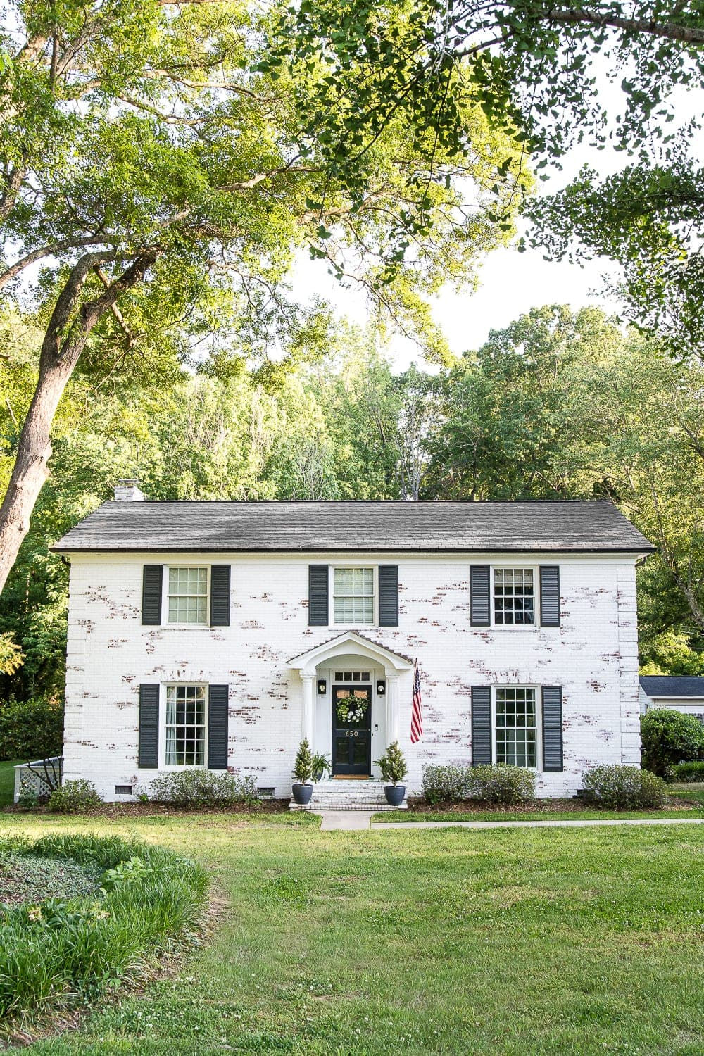 Limewashed white colonial house with black shutters