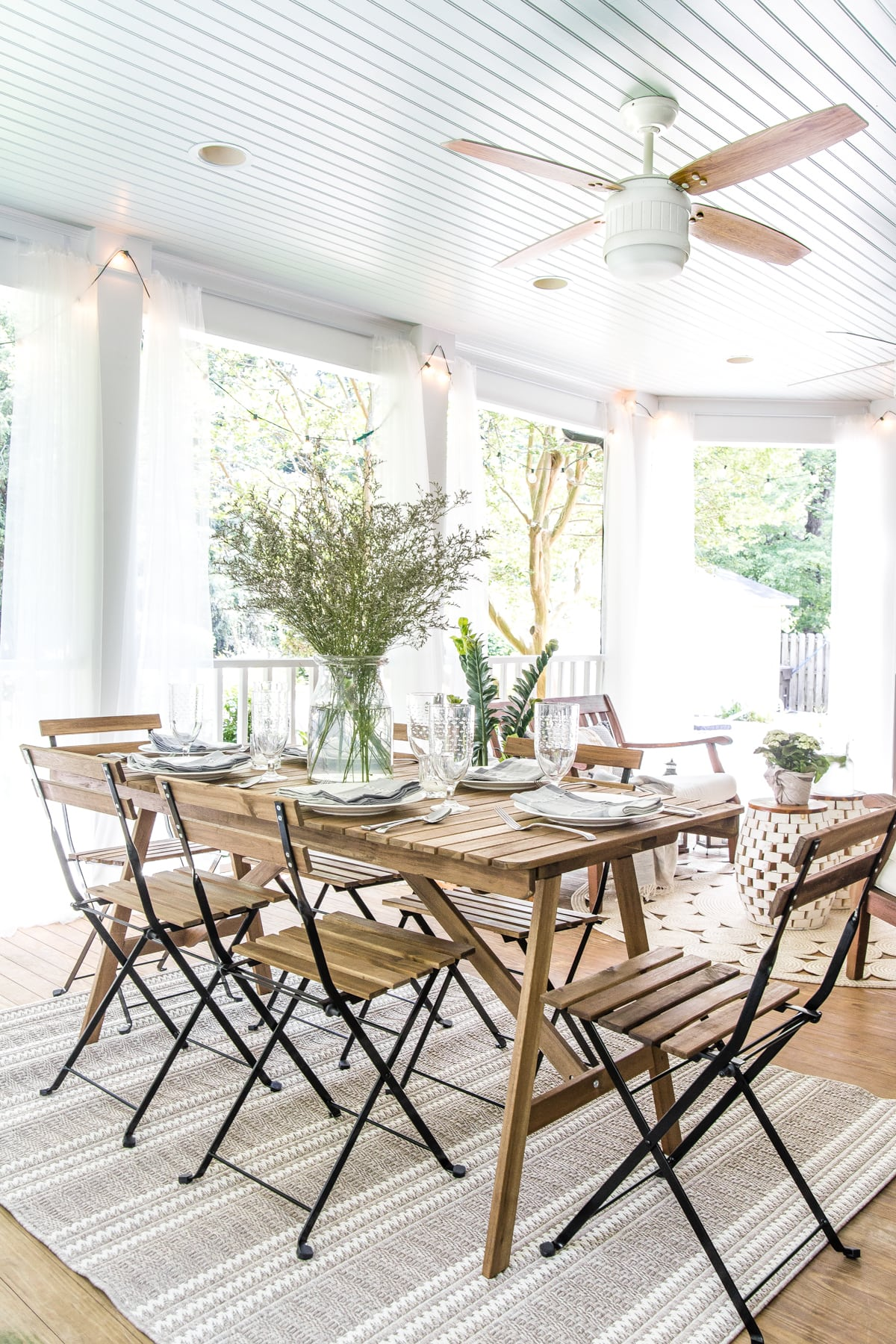 outdoor dining table on back porch with haint blue ceiling and ceiling fan