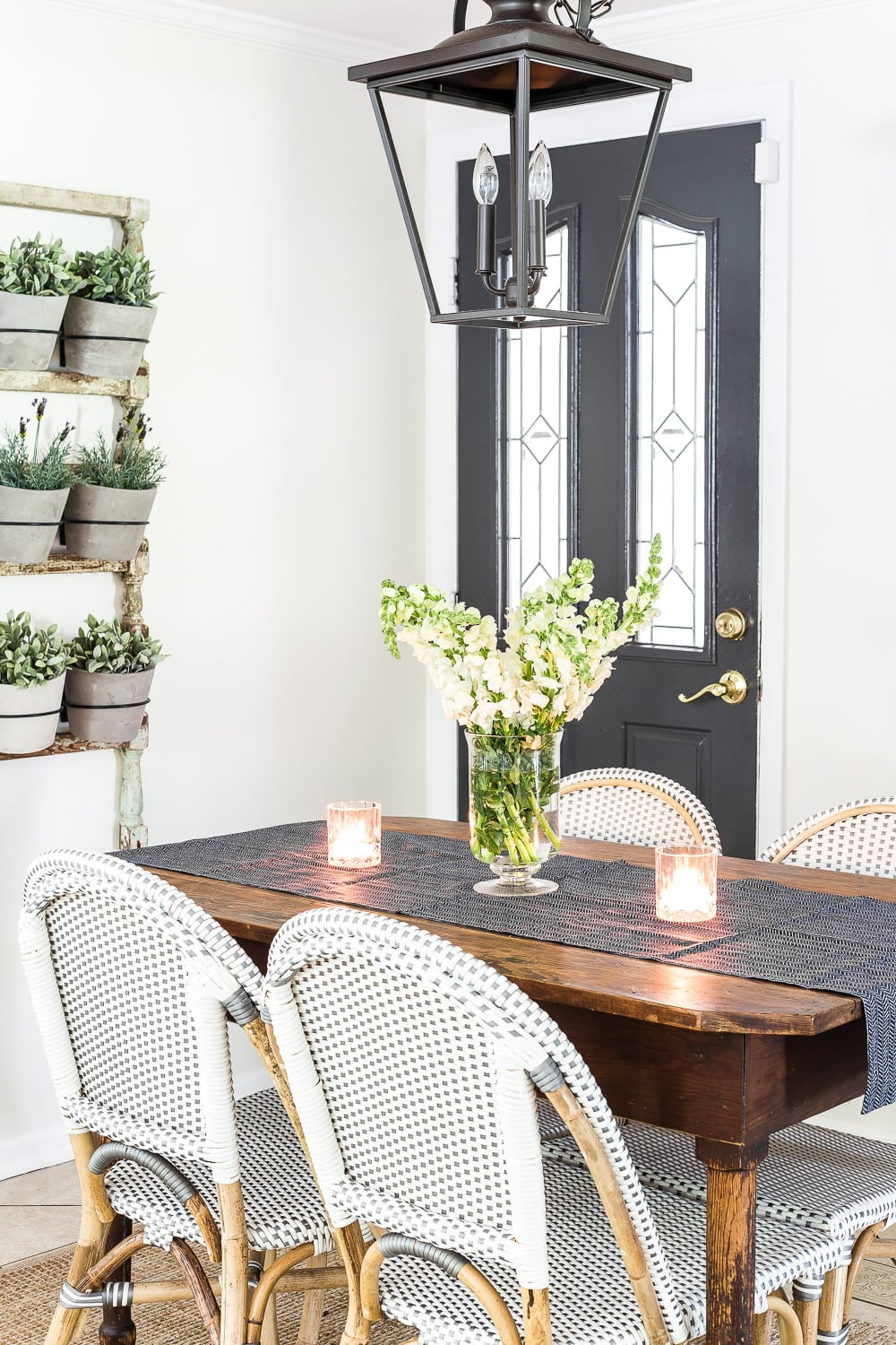 breakfast nook decorated for summer with greenery, blue, and neutrals