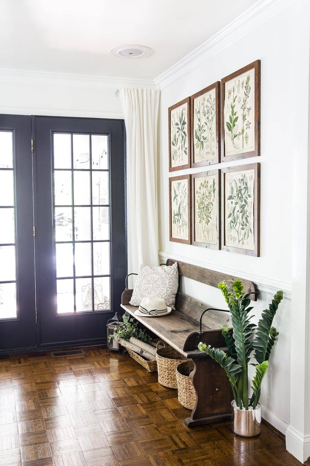 entryway with summer botanical gallery wall and reclaimed wagon bench
