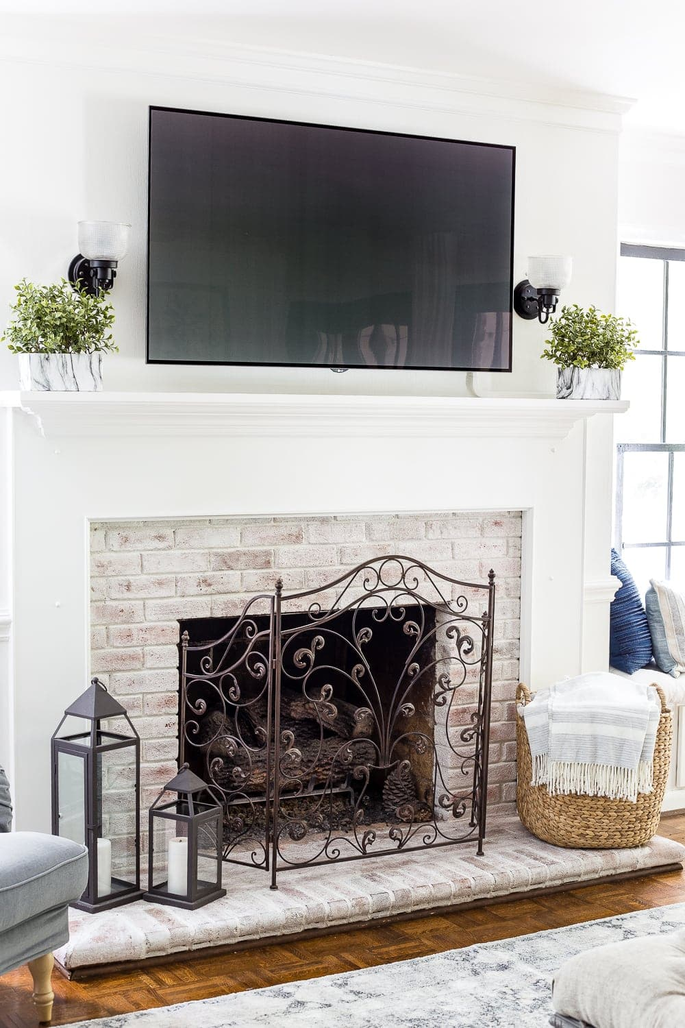 limewashed brick fireplace with tv above mantel
