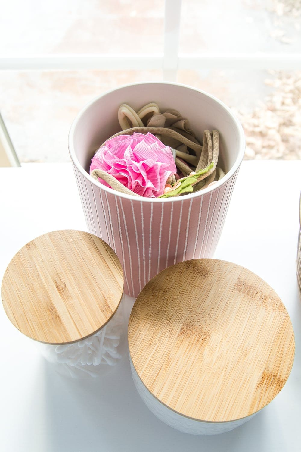 Nursery Organization | Use lidded canisters from the kitchenware aisle to store headbands and bows.