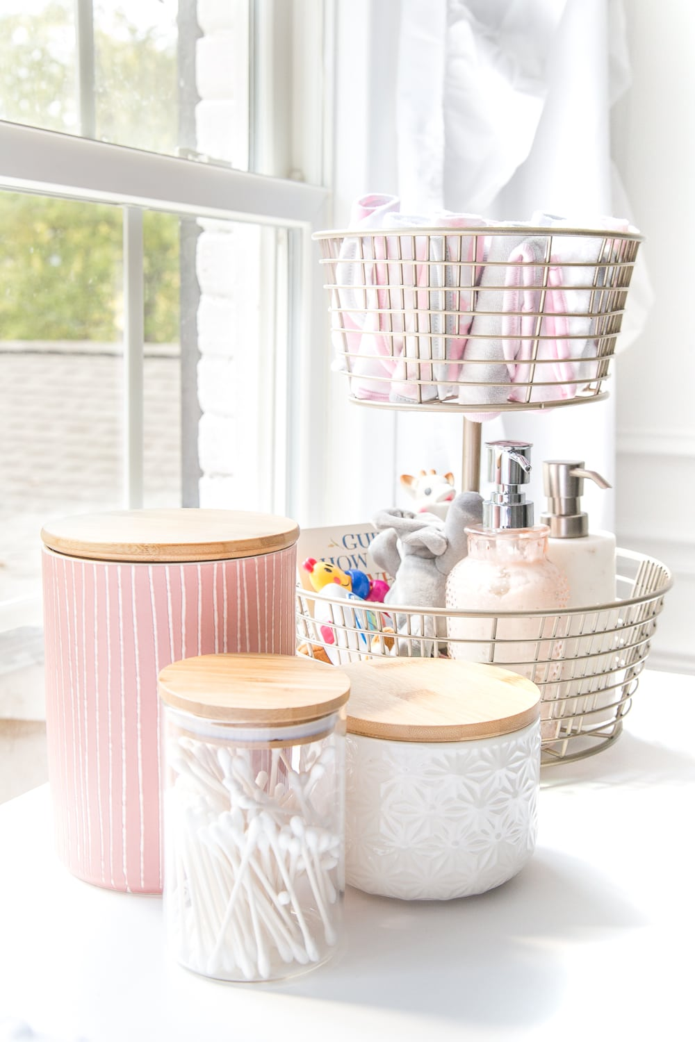 Nursery Organization | Use a tiered fruit basket from the kitchenware aisle to store baby washcloths, grabby toys, Wubbanubs, lotion, and hand sanitizer and lidded kitchen canisters to store Q-tips, pacifiers, and hair bows.
