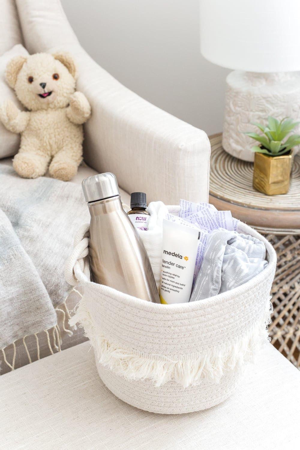 Nursery Organization | Breastfeeding basket to keep beside a chair filled with nursing pads, water bottle, lanolin, burp cloths, nursing cover, and lavender essential oil.