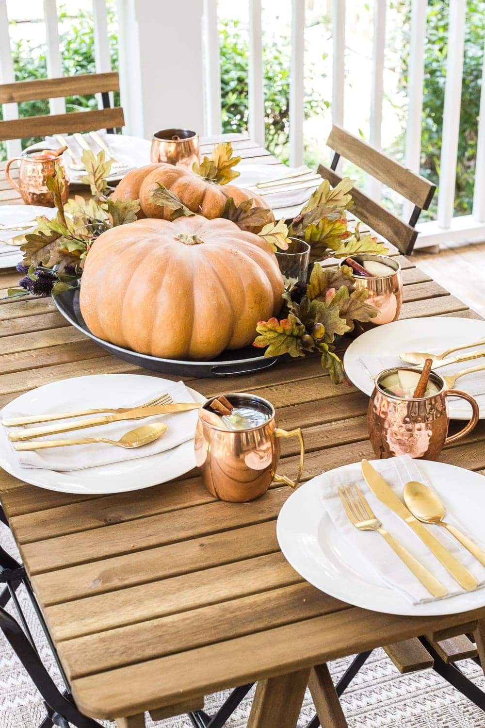 cozy fall porch with copper and pumpkin tablescape