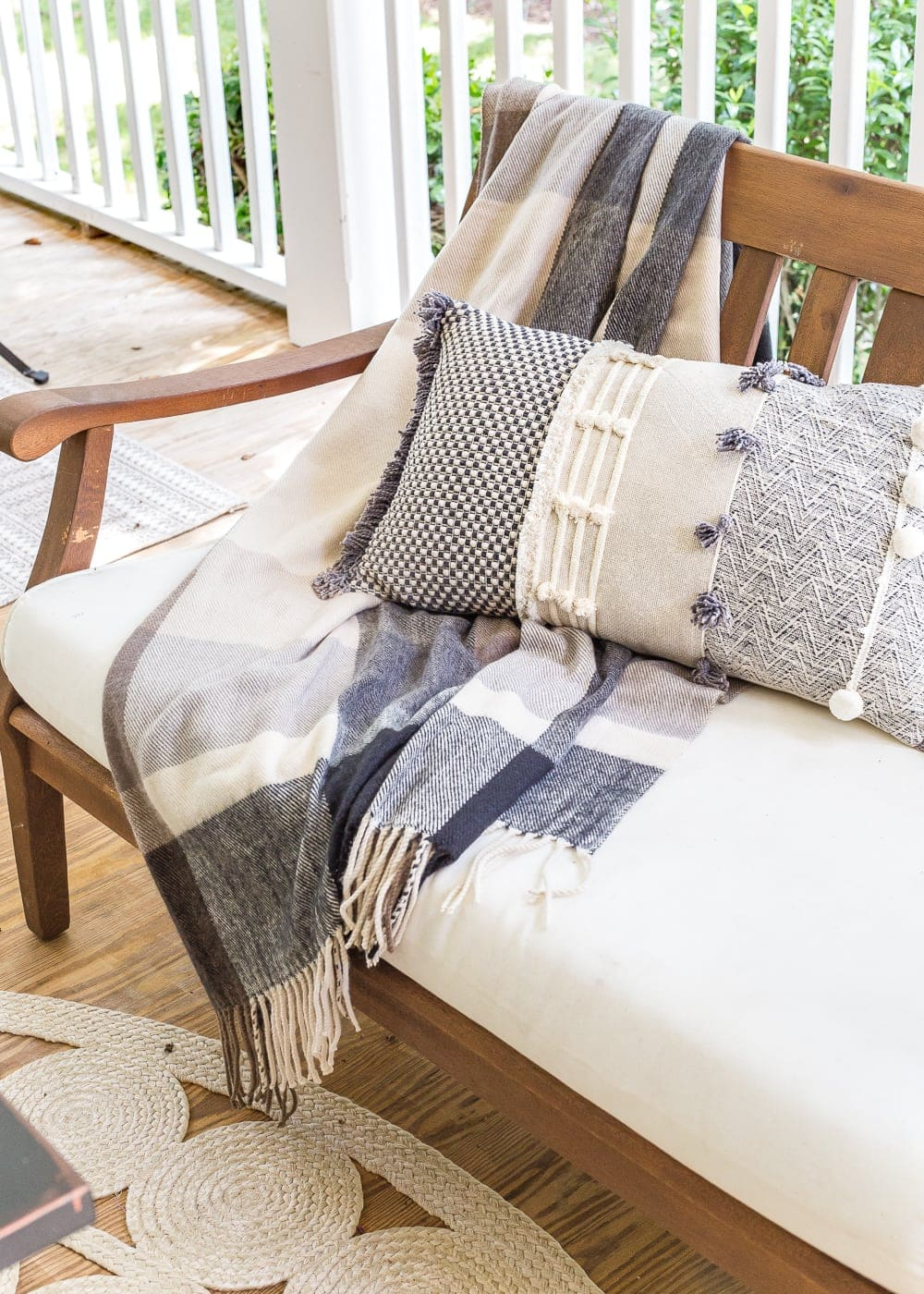 cozy fall porch with plaid throw blanket and textured pillow