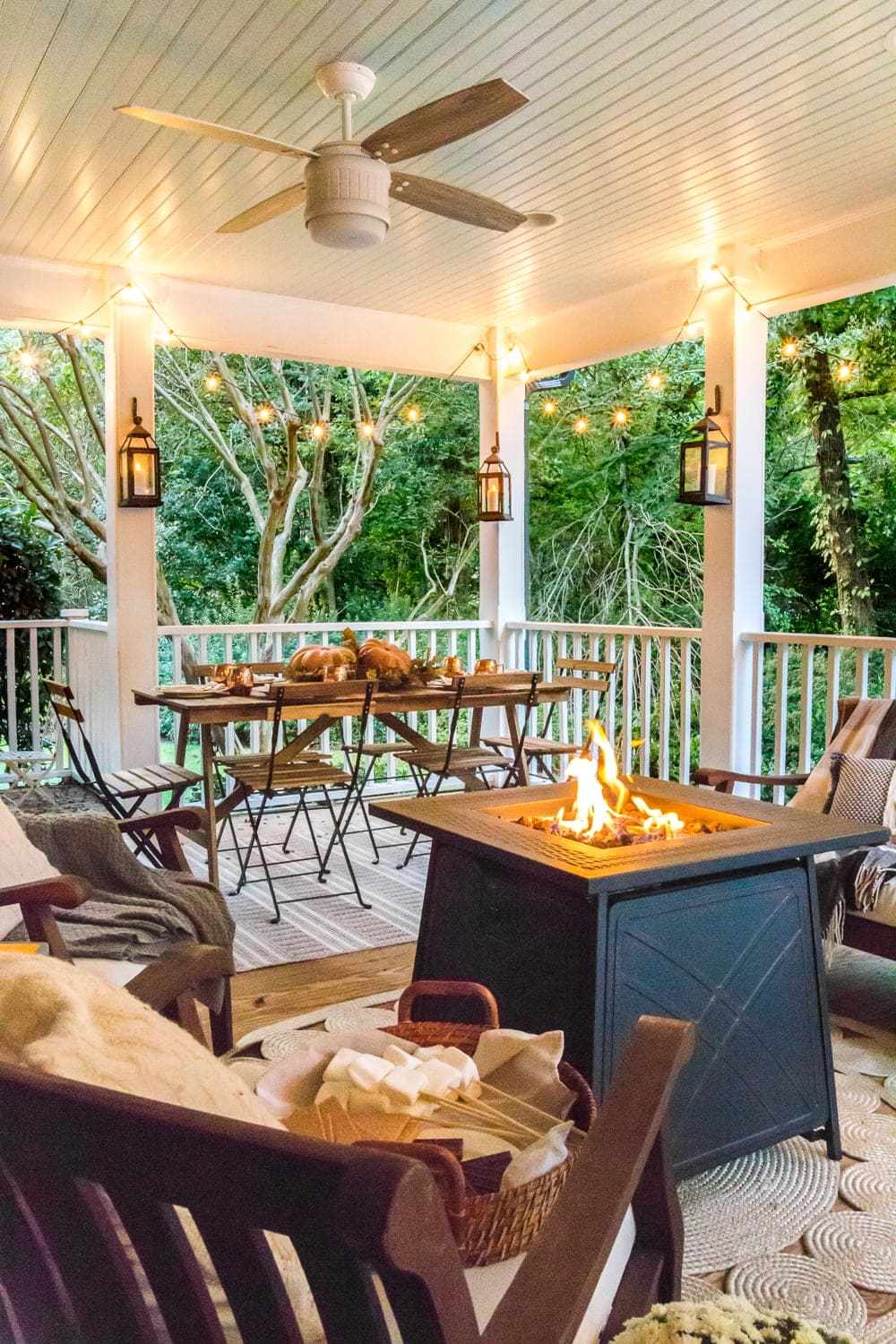 cozy fall porch with lanterns, string lights, and fire pit
