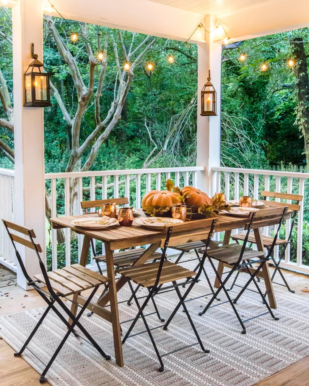 cozy fall porch dining with lanterns and string lights