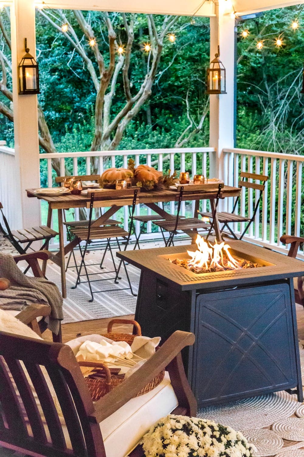 cozy fall porch with fire pit, string lights, and lanterns