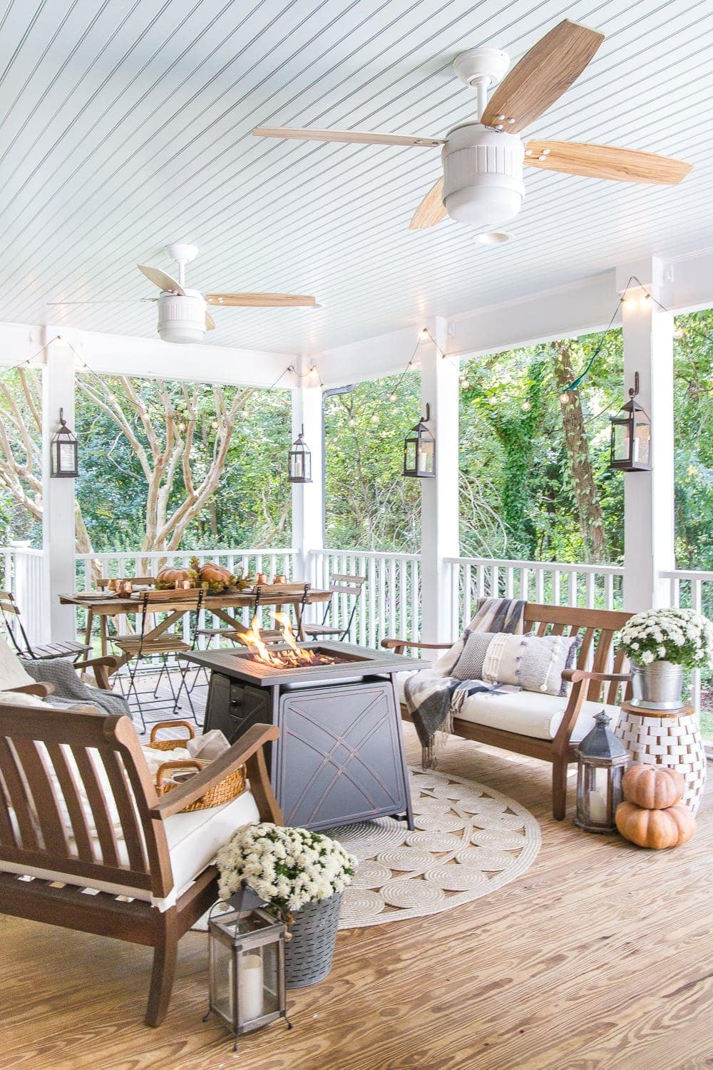 Cozy fall porch with pumpkins, a gas fire pit, lanterns and string lights