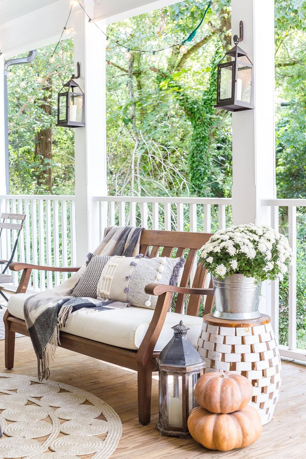 cozy fall porch with plaid throw blankets, textured pillows, pumpkins, lanterns, mums, and string lights