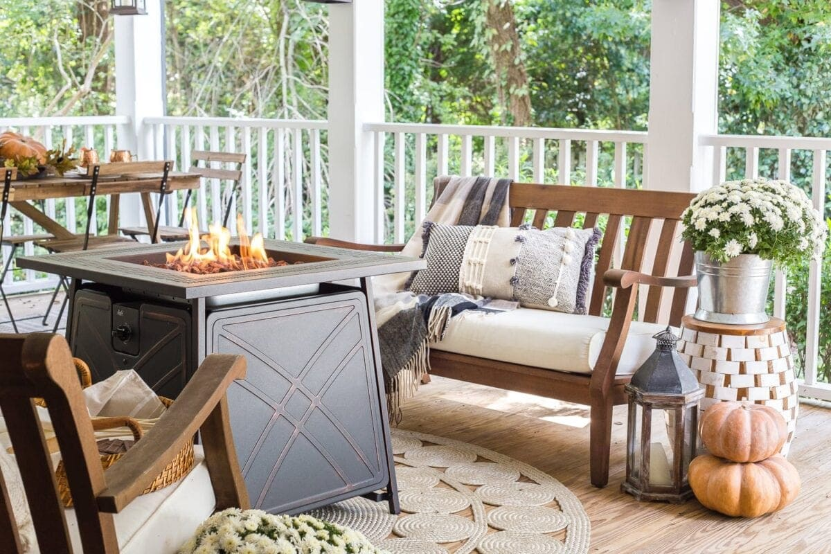 Cozy fall porch with gas fire pit, pumpkins, and mums