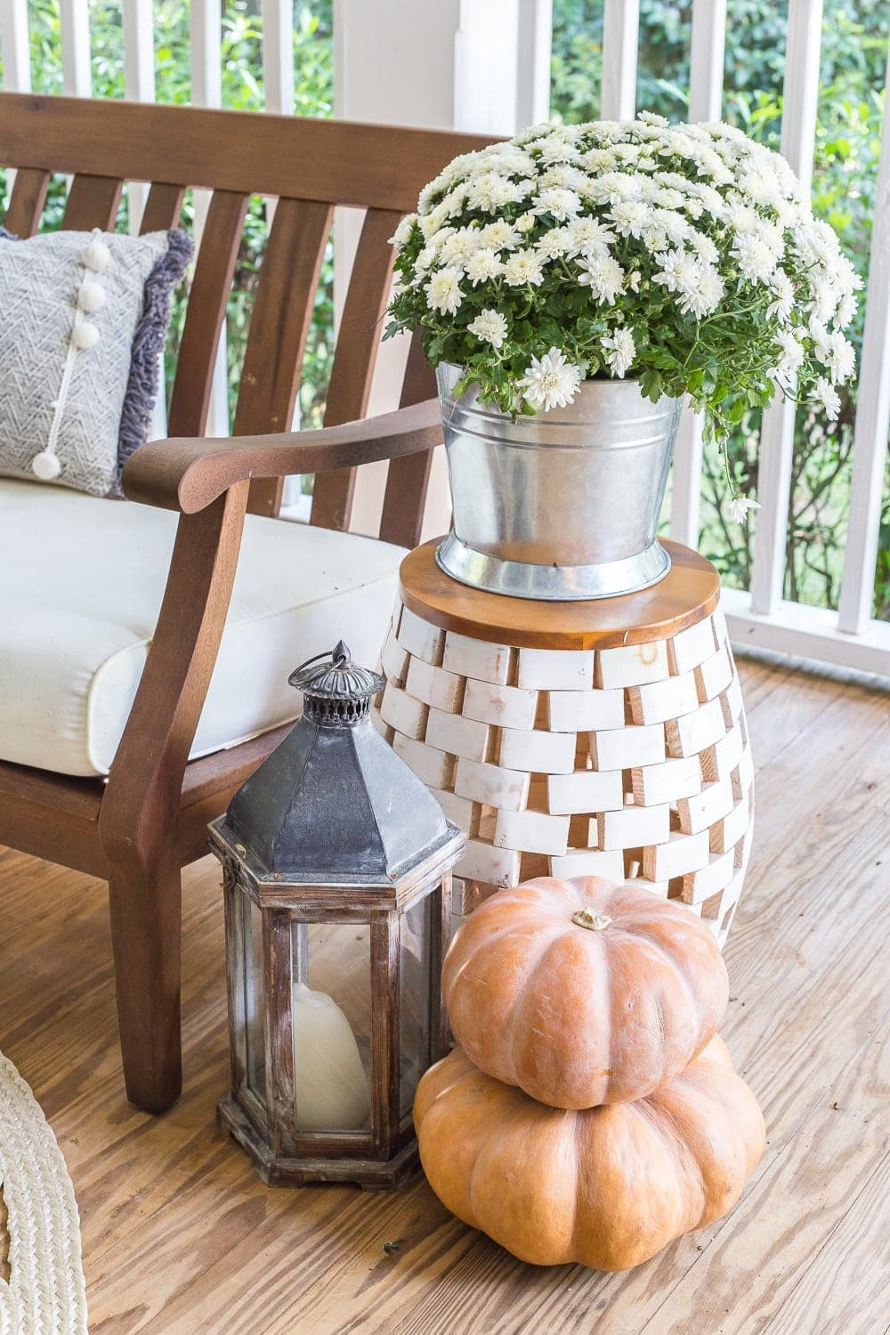 cozy fall porch with lanterns, mums, and pumpkins