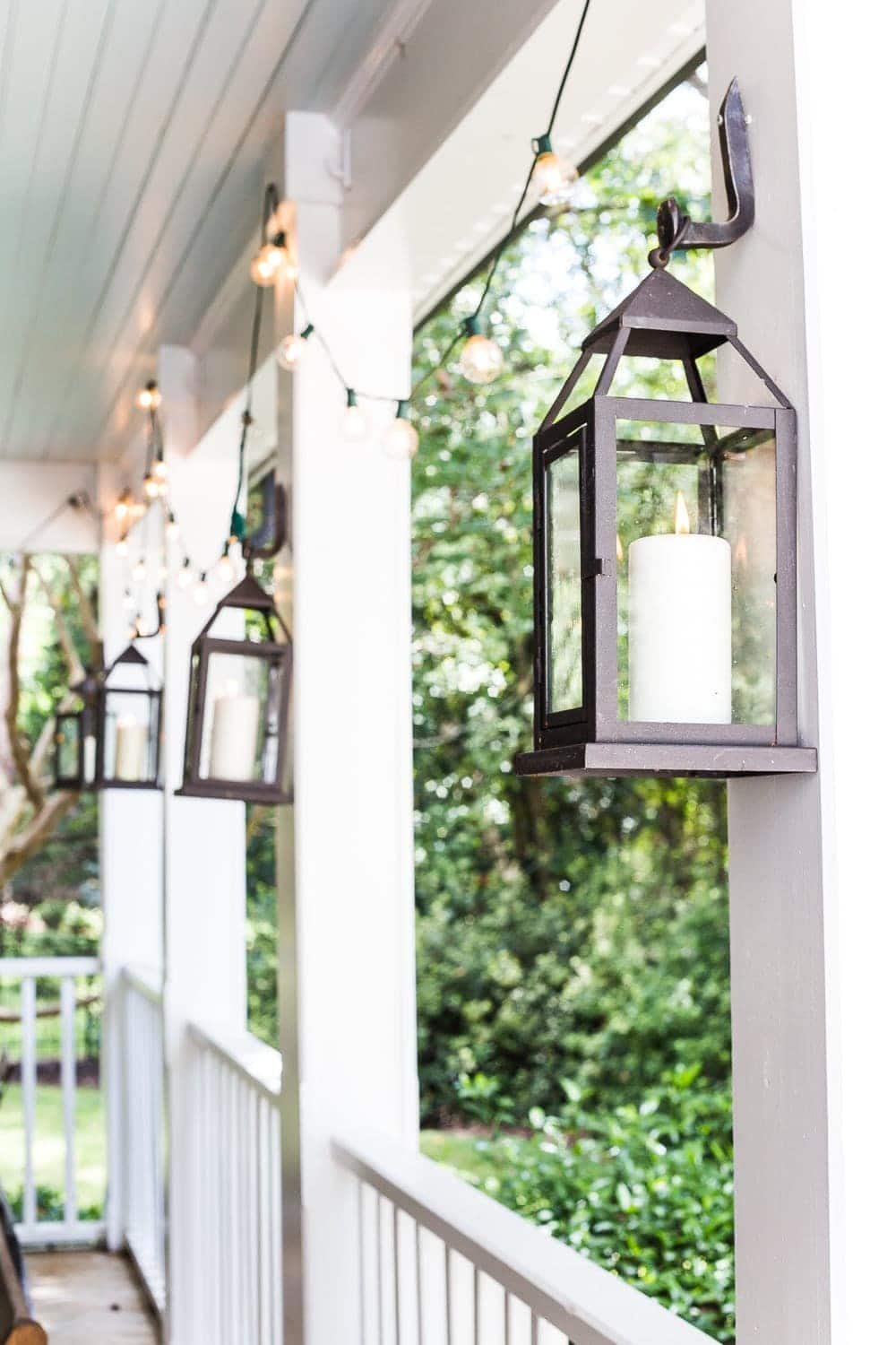 cozy fall porch with string lights and outdoor lanterns