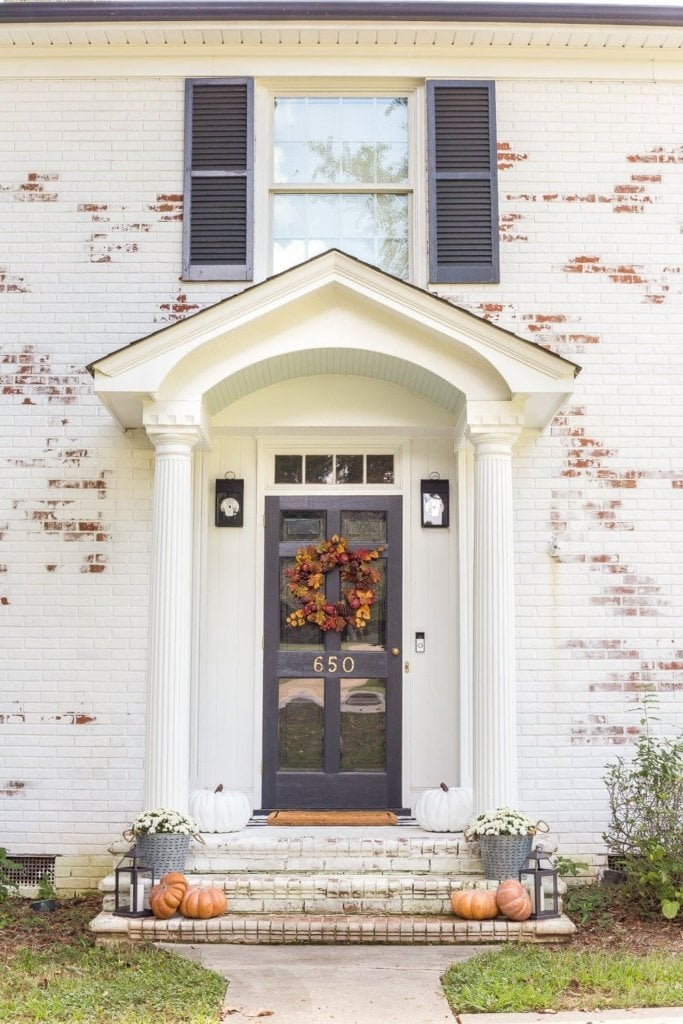 A simple colonial fall front porch stoop with traditional orange and yellow colors and home decor accents. #fallfrontporch #fallporch
