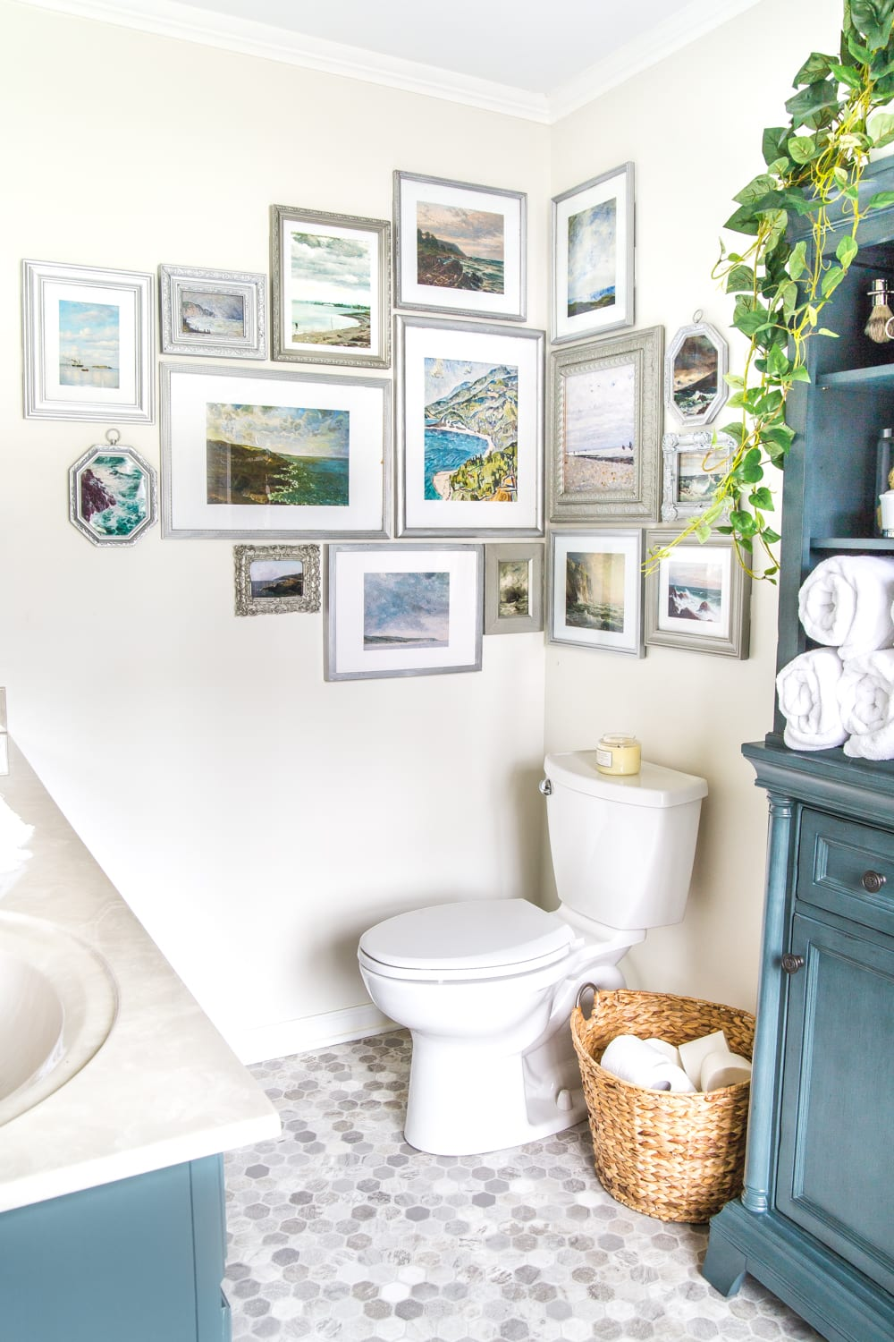 A free printable set of a coastal gallery wall featuring antique ocean paintings and how to frame them inexpensively with thrifted finds. #coastaldecor #gallerywall #bathroomart #bathroomwall #bathroomdecor #coastalart