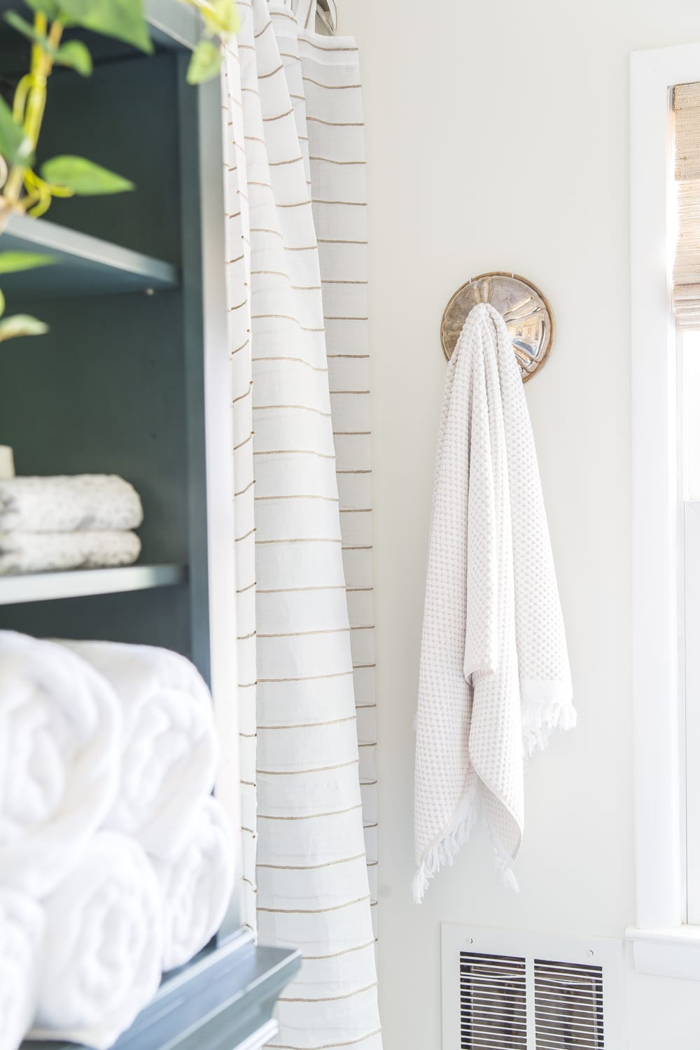 A thrifty solution for using leftover chafing dish lids as towel hooks in a bathroom. #bathroomdecor #wallhooks #towelhooks #chafingdishlid