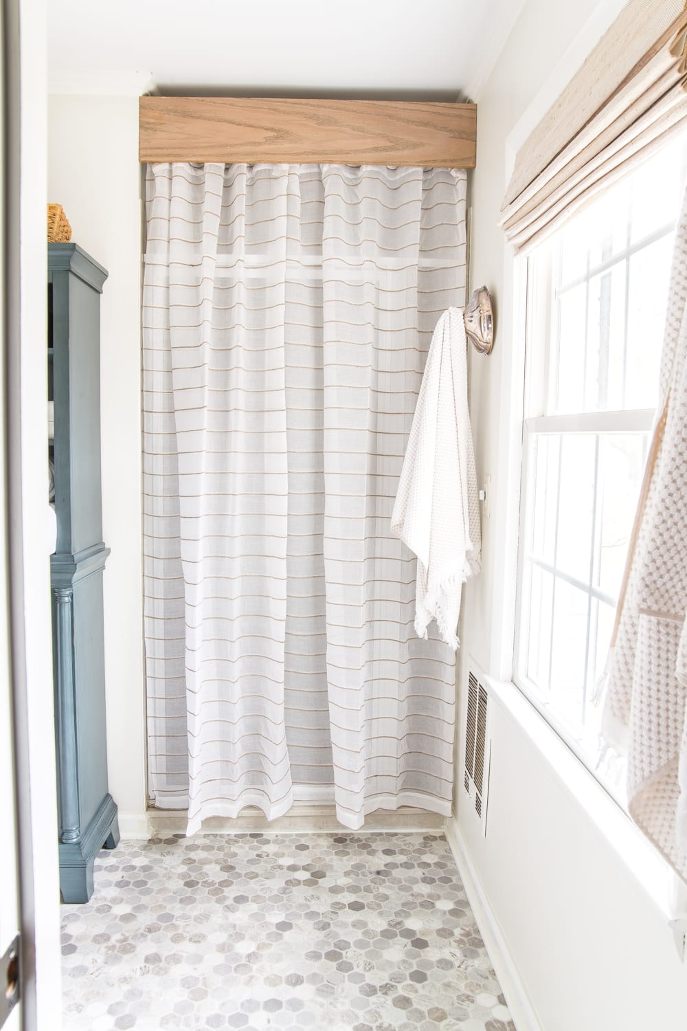 Budget Master Bathroom Refresh Reveal | old shower door cover-up with a semi-sheer curtain and a DIY wooden cornice