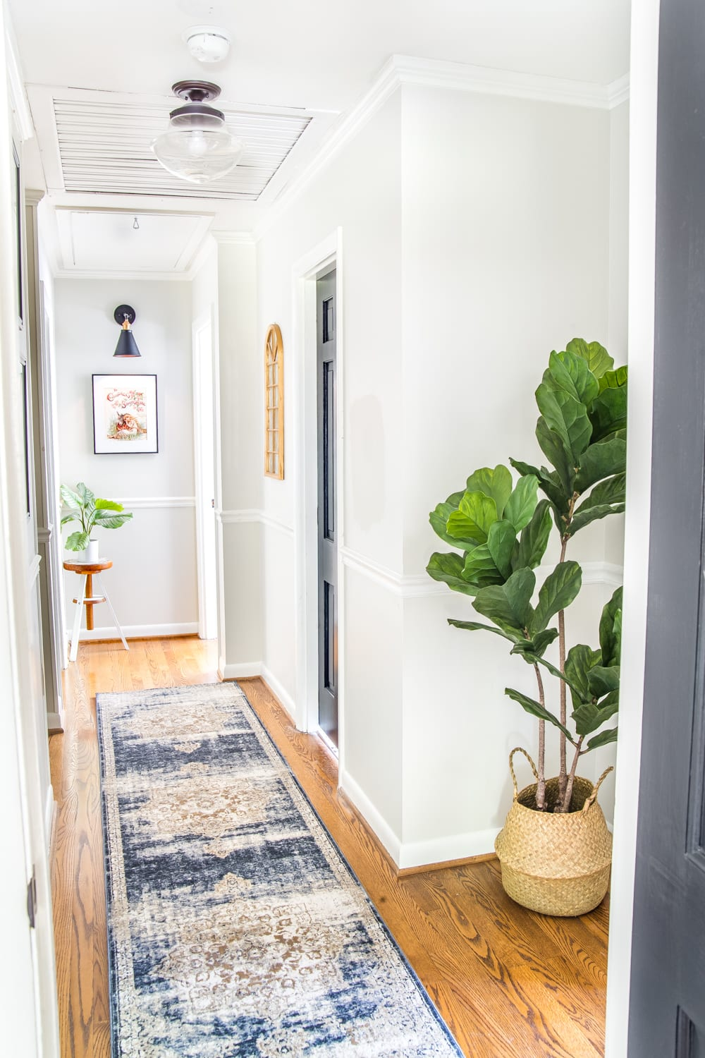 6 Tips to Decorate a Boring Hallway | blesserhouse.com - light gray painted hallway with black doors, runner rug, new lighting, and plants