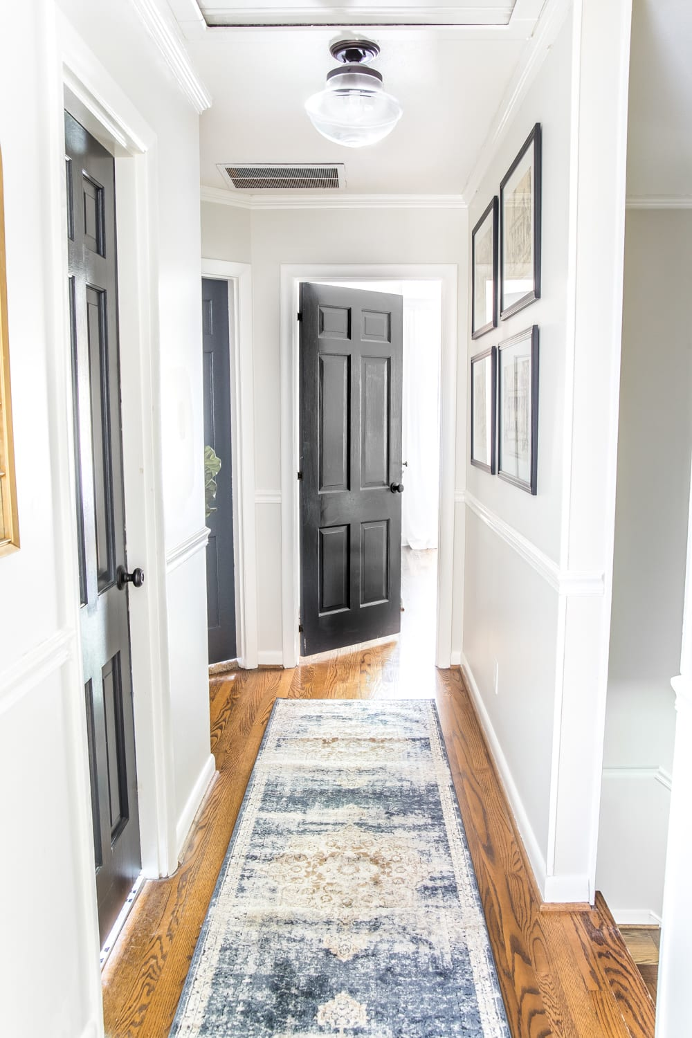 6 Tips to Decorate a Boring Hallway | blesserhouse.com - light gray painted hallway with dark charcoal doors, a runner, new lighting, and wall decor