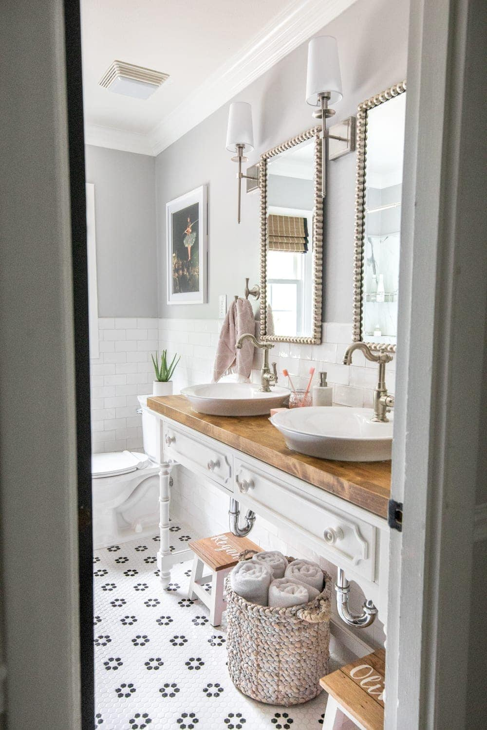 Whimsical, classic kids bathroom makeover | open vanity table with step stools and vessel sinks