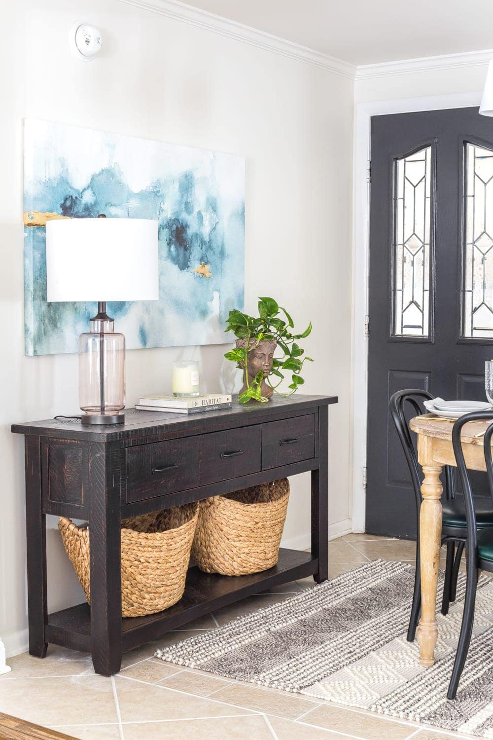 A console table beside an entry door in a breakfast nook to maximize on storage without the use of a mudroom.