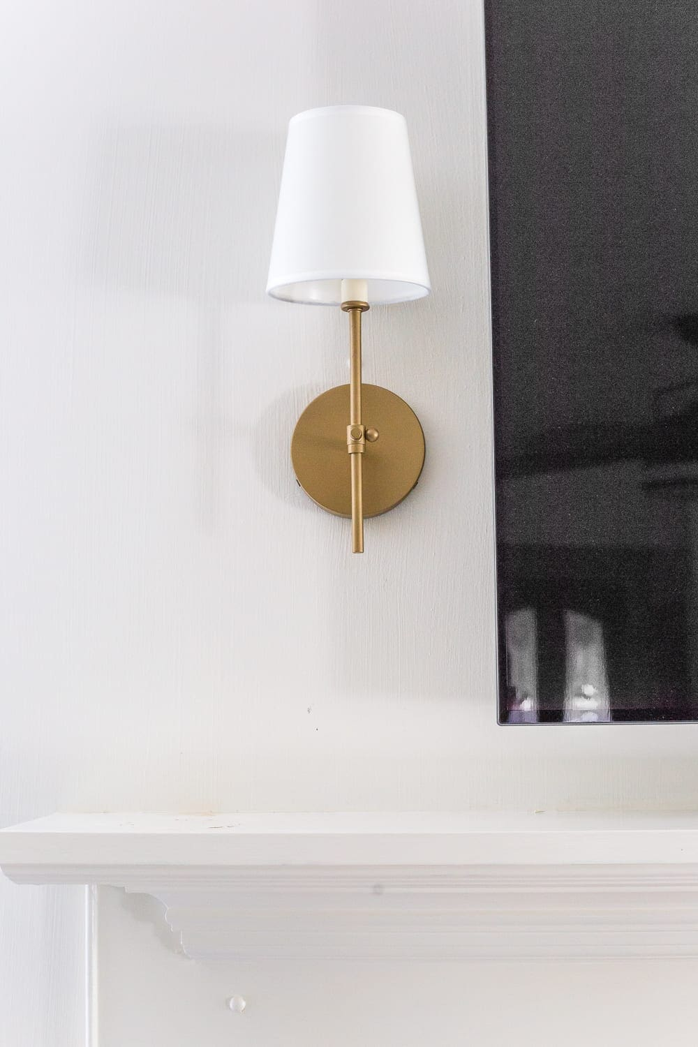 Keep your mantel simple with just a pair of sconces on either side of your TV.
