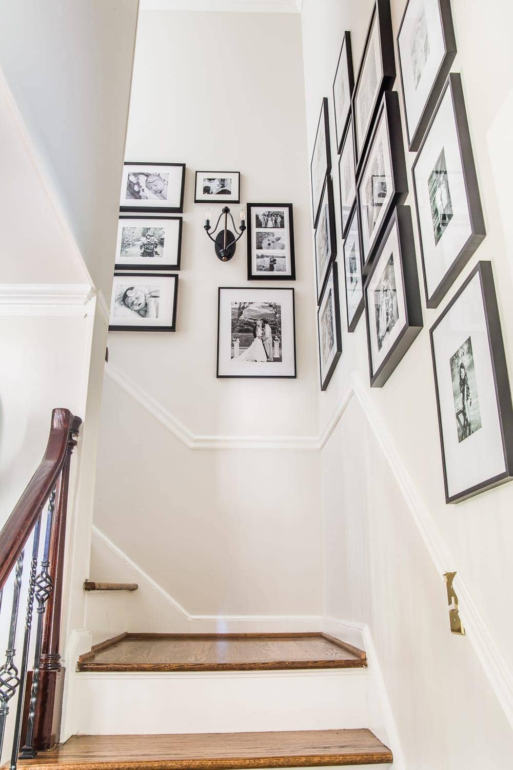 How we hung our stairway gallery wall quickly and easily without any accidental nail holes + inspiration for other gallery walls in the house. #gallerywall #stairwaygallerywall #familygallerywall #staircasegallerywall #foyer #entryway