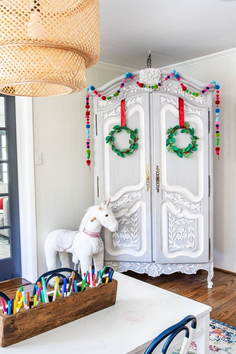Colorful Christmas Playroom | Pom pom garland and felt wreaths on wardrobe reading nook cabinet