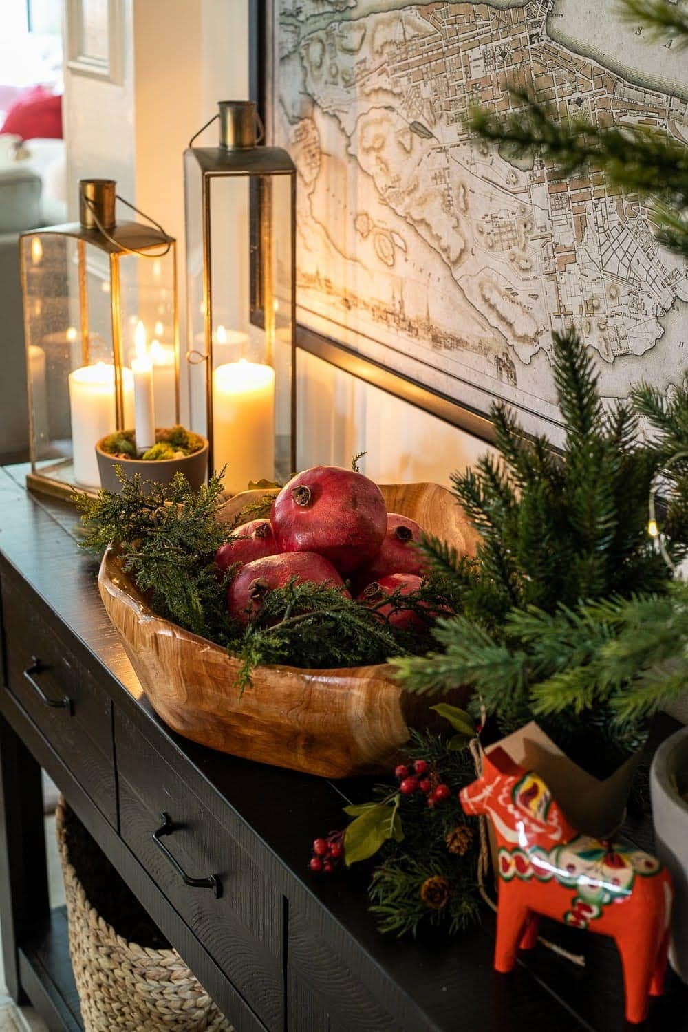 Swedish Christmas with Dala horse, candlelight, and pomegranates in a bowl.