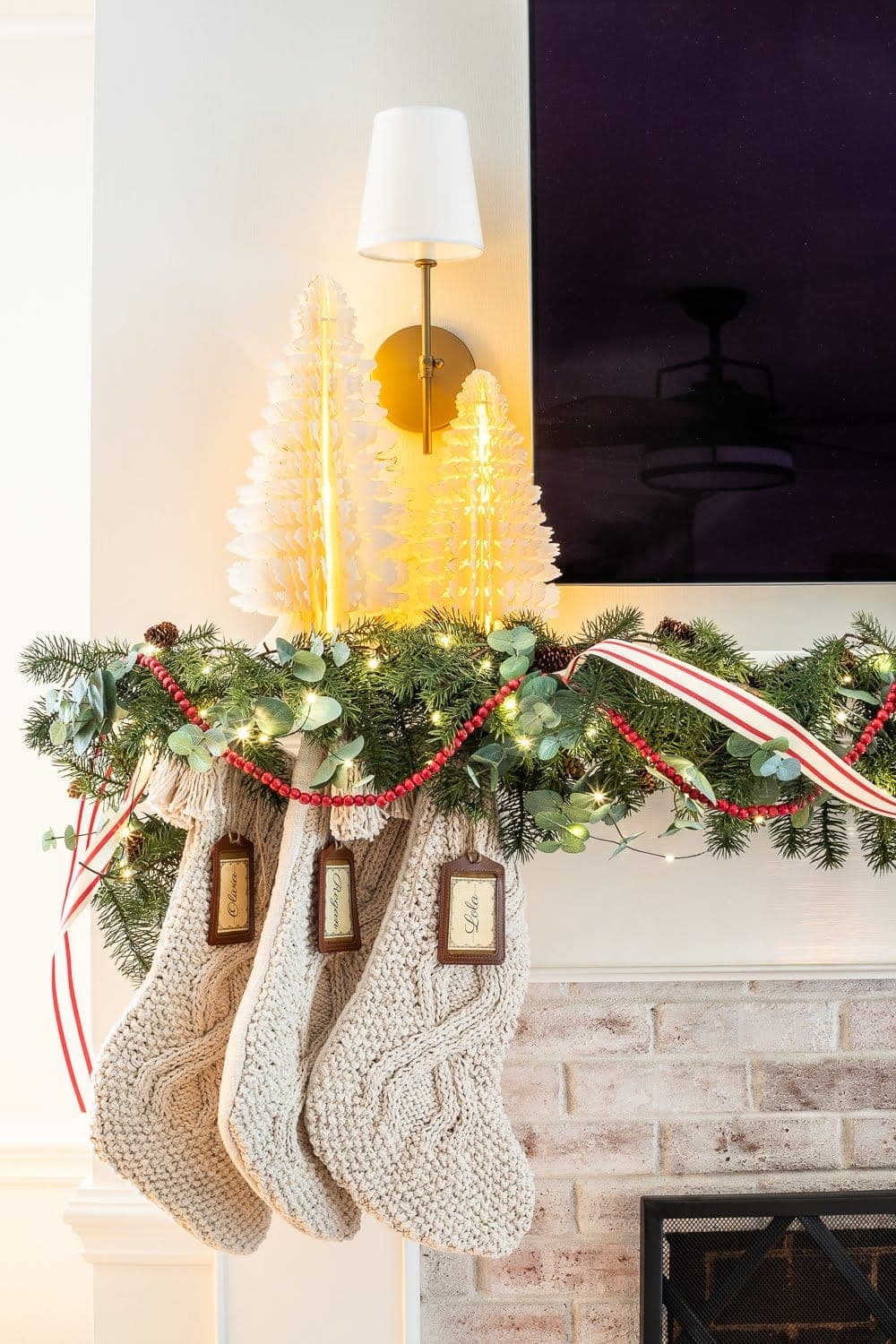Swedish Christmas with paper tree figurines, chunky knit stockings, abundant greenery, fairy lights, and pops of red
