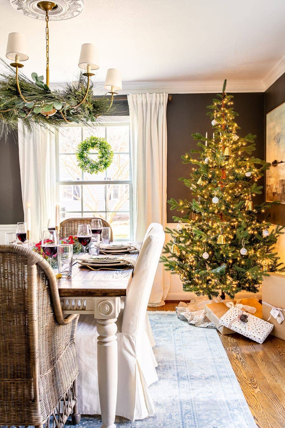 Christmas decorating ideas | Christmas tree in the dining room with garland on a chandelier and wreaths on windows