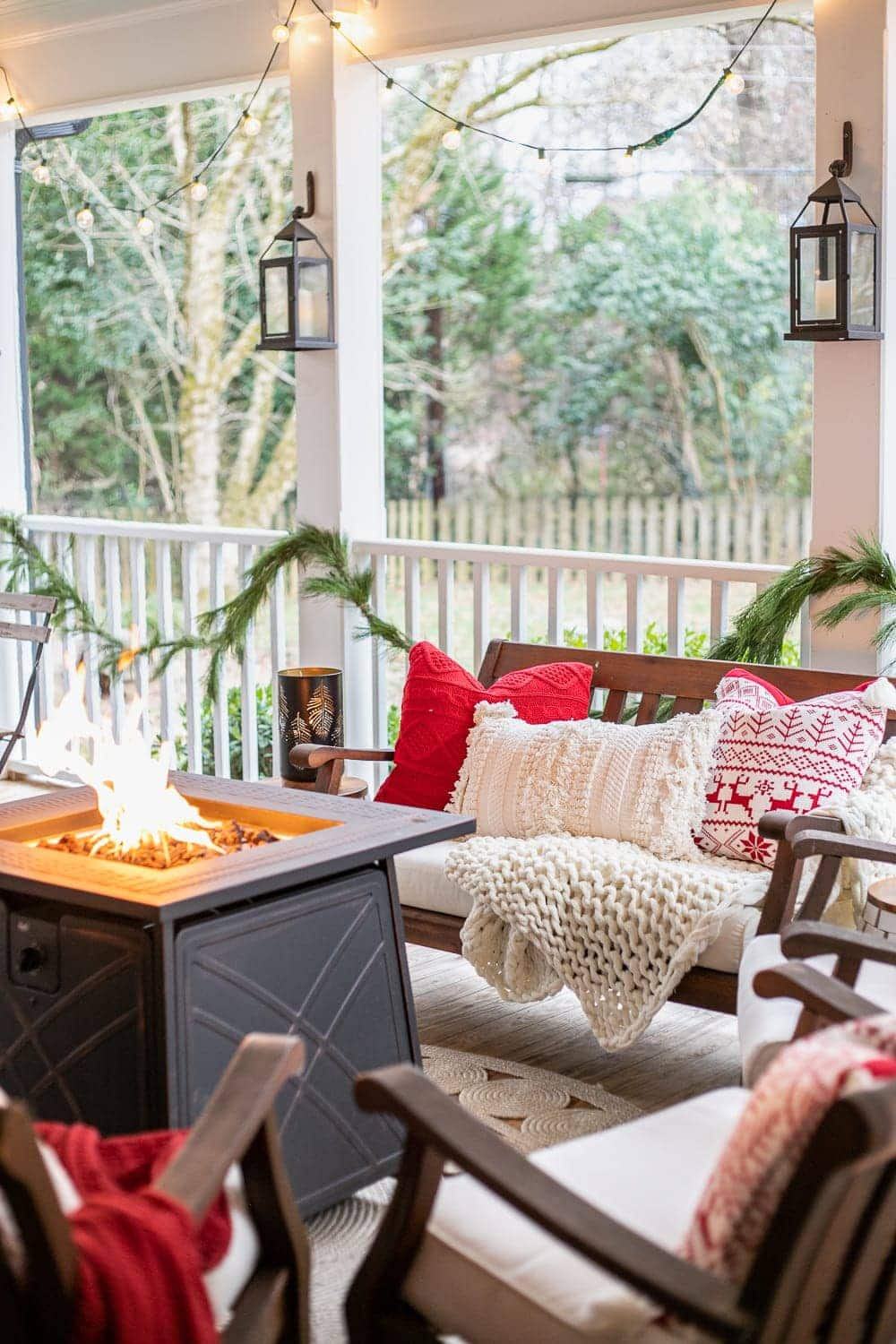 Cozy Christmas back porch with fire pit table, lanterns, and string lights