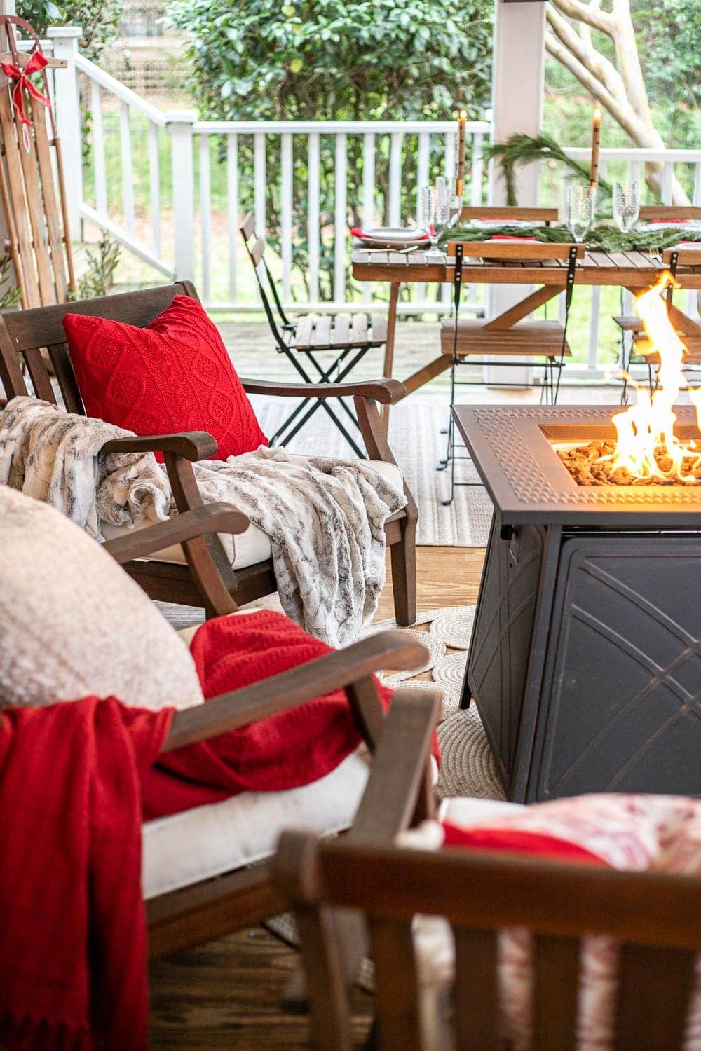 Cozy Christmas back porch with red blankets and pillows and a fire pit table