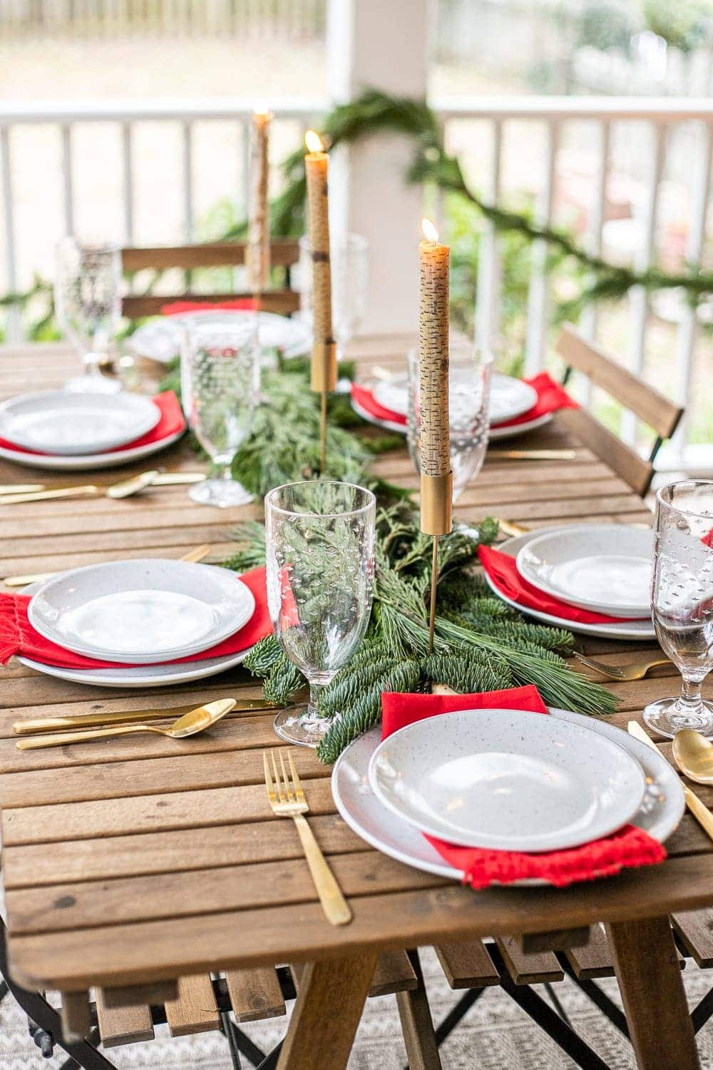Christmas outdoor tablescape with fresh greenery and birch candles