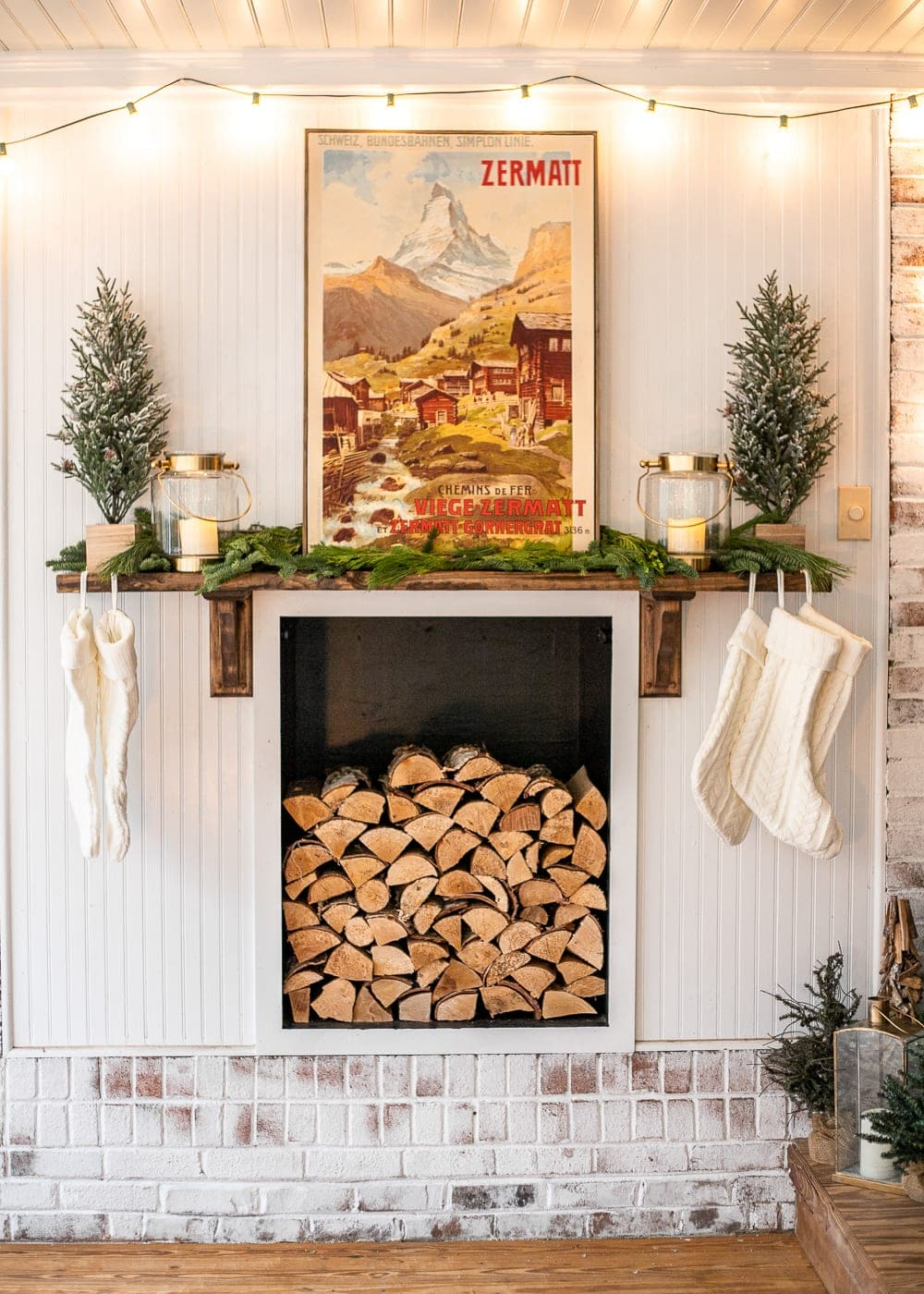 DIY faux fireplace decorated for Christmas with wood stack, vintage poster, mini trees, stockings, fresh greenery, lanterns, and string lights