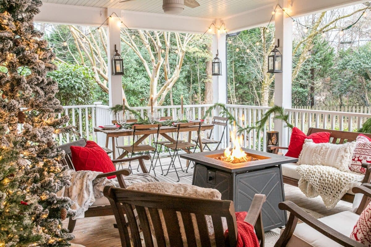 Cozy Christmas back porch with fire pit table, outdoor seating, and an outdoor dining space