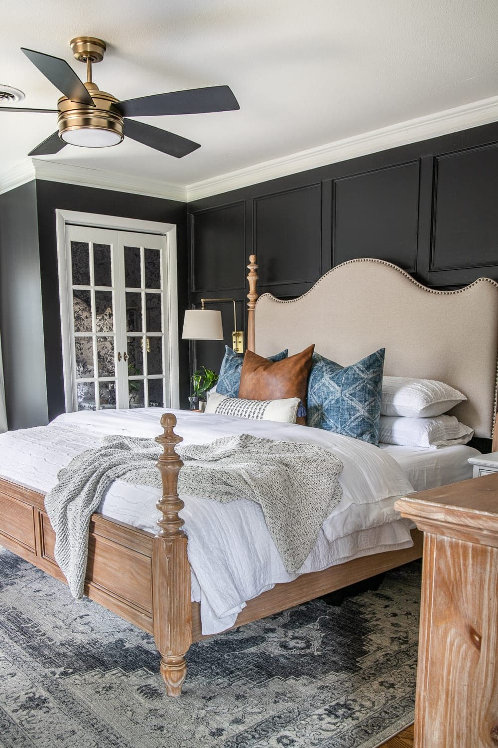 A plain, dated master bedroom gets a modern vintage makeover with moody black paint, modern pillows, vintage style furniture, and budget DIY grid molding focal wall.