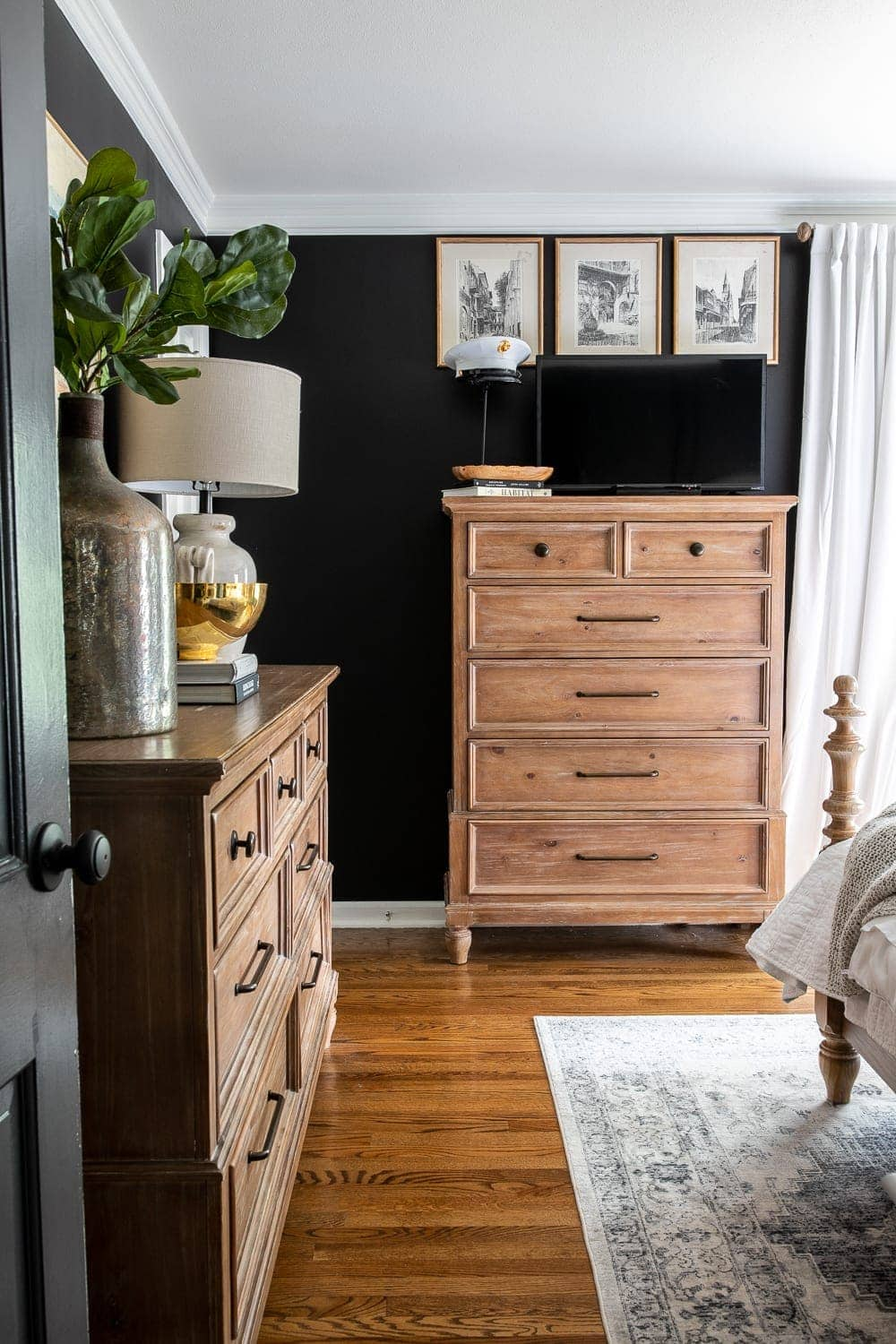 moody modern vintage master bedroom with black paint and TV on top of dresser