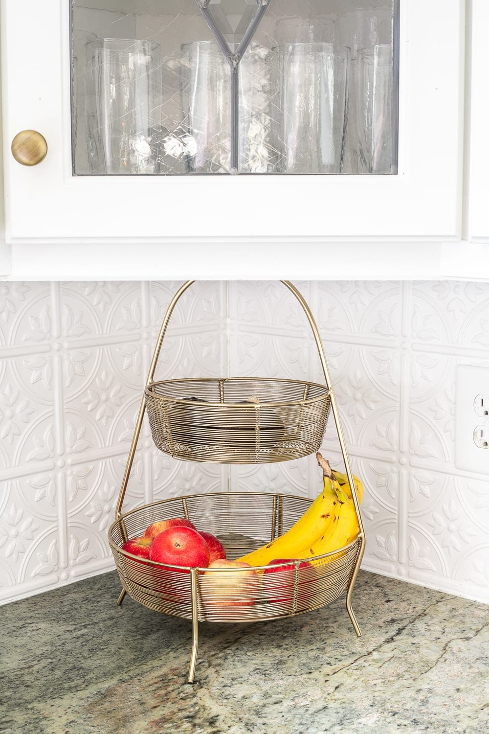 tiered basket for holding fruit on a kitchen countertop