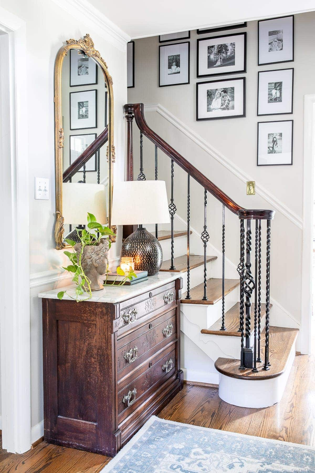 Classic timeless modern foyer with stairway gallery wall and chest with mirror