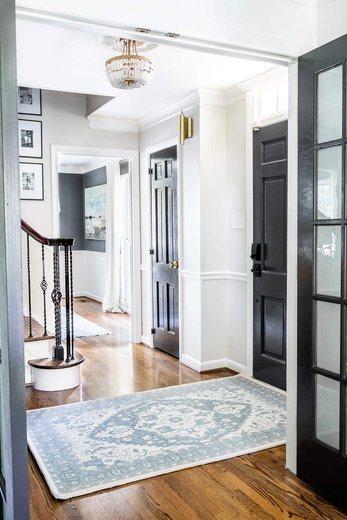 Classic timeless modern foyer with black doors