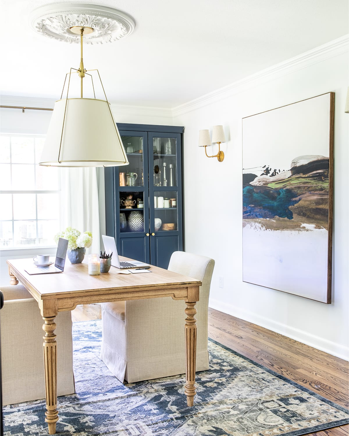 home office decor with work table, pendant light, large scale art, upholstered rolling desk chairs, and storage cabinets